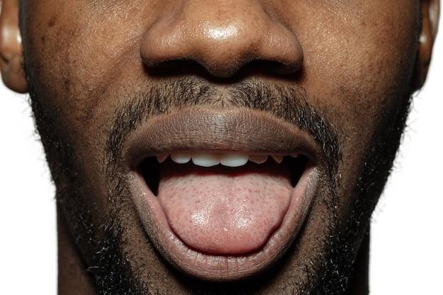 Gremacing. nahaufnahme des gesichts des schönen afroamerikanischen jungen mannes, fokus auf den mund. menschliche emotionen, gesichtsausdruck, kosmetik, körper- und hautpflegekonzept. spaß, streckt die zunge raus.