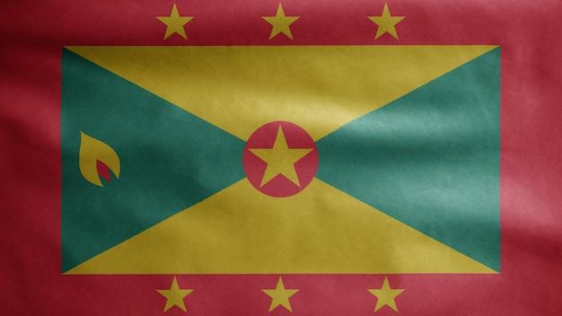 Grenadische flagge weht im wind. nahaufnahme von grenada banner weht, weiche und glatte seide. stoff textur fähnrich hintergrund. verwenden sie es für das konzept für nationalfeiertage und länderanlässe.