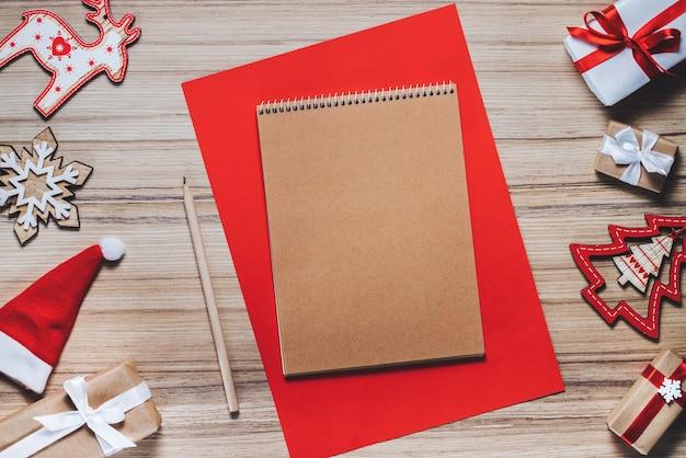 Grenze der feiertagsdekorationen, des spielzeugs und des leeren bastelpapier-skizzenbuchs auf hölzernem hintergrund