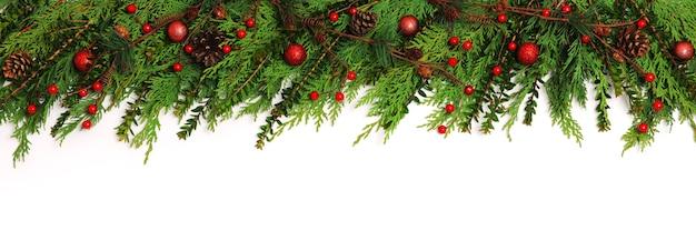 Grenze der grünen zweige mit weihnachtsdekoration auf weiß