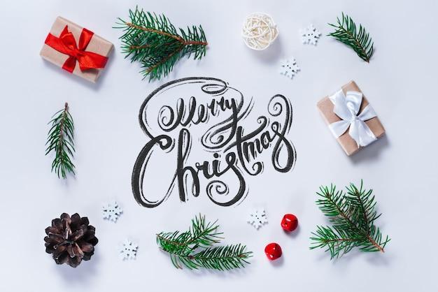Grenze der neujahrsdekorationen und der kiefernzweige auf weißem hintergrund mit frohen weihnachtswünschen geschrieben mit kalligraphischer schrift