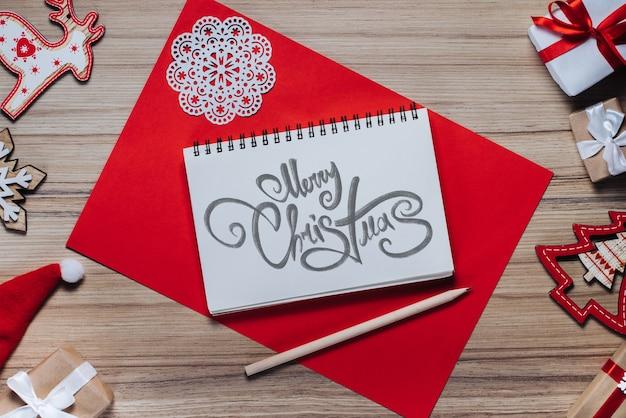 Grenze der neujahrsdekorationen und -geschenke auf hölzernem hintergrund mit frohen weihnachtswünschen geschrieben mit kalligraphischer schrift