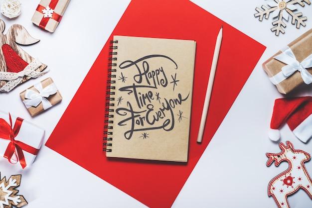 Grenze der neujahrsdekorationen und -geschenke auf weißem hintergrund mit frohen weihnachtswünschen geschrieben mit kalligraphischer schrift am geöffneten notizbuch