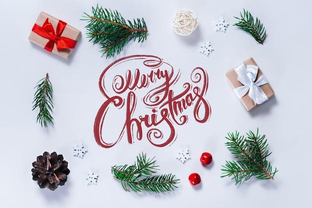 Grenze der neujahrsdekorationen und -geschenke auf weißem hintergrund mit frohen weihnachtswünschen geschrieben mit kalligraphischer schrift Premium Fotos