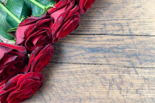 Grenze der roten rosen am hölzernen hintergrund des schmutzes