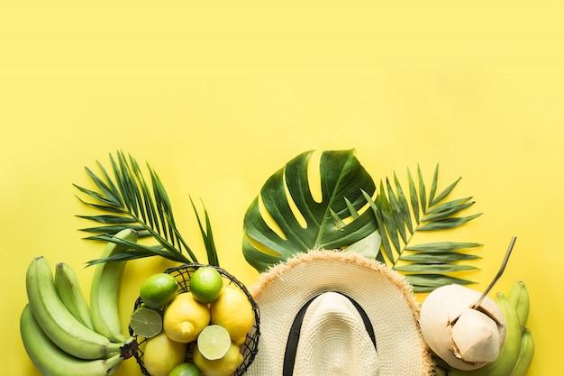 Grenze des tropischen strandoutfits, des weiblichen zubehörs, des strohsonnenhutes, der monstera-blätter auf gelb. sommerkonzept.