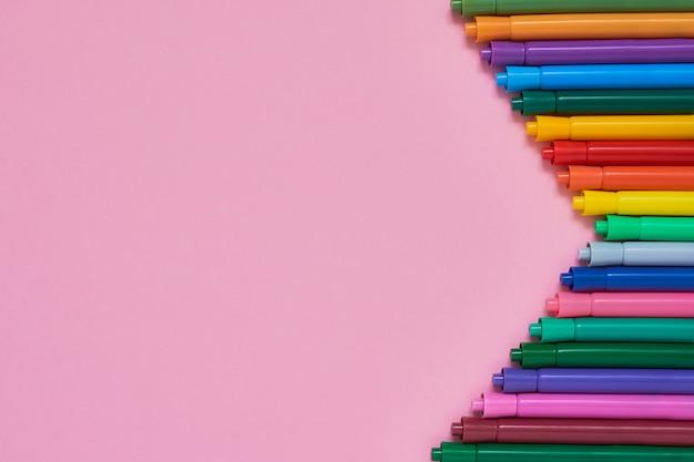 Grenze von farbigen filzstiften auf rosa hintergrund mit copyspace. ansicht von oben