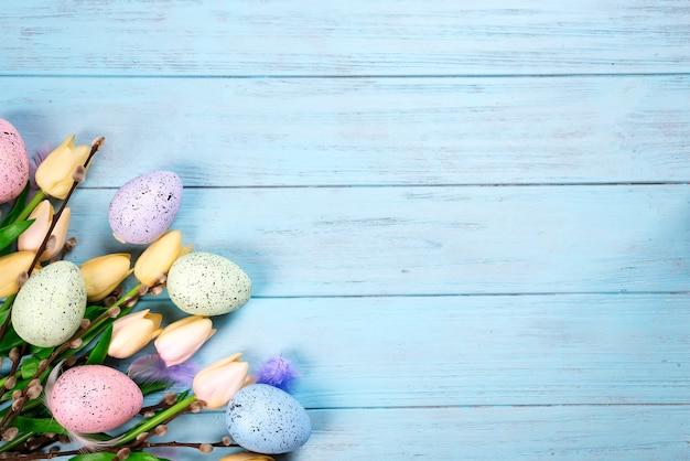 Grenze von frühlingstulpen mit niederlassungen der dichtung und der bunten eier auf blauem hölzernem hintergrund