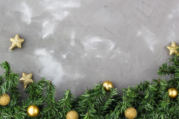 Grenze von tannenzweigen und goldenen weihnachtskugeln und sternen.