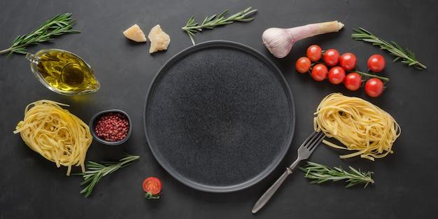 Grenze von trockenen rohen teigwarenbandnudeln, tomaten, basilikum, parmesankäse.