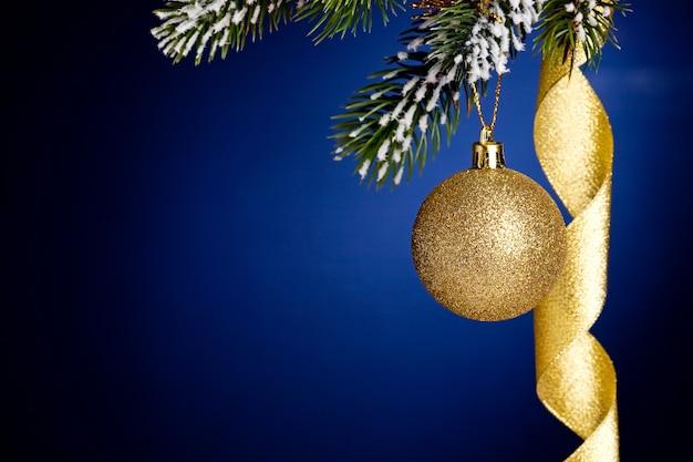 Grenze von weihnachtsbaumast und dekorationen auf dunkelblauem hintergrund