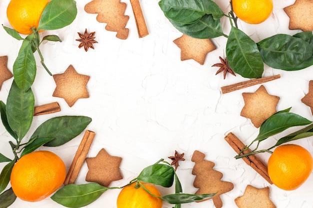 Grenze von weihnachtssternplätzchen mit gewürzen und mandarine auf weißem rahmenhintergrund mit copyspace,
