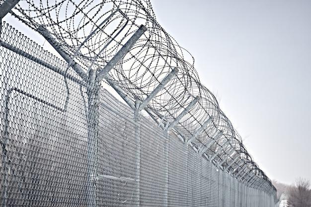 Grenzzaun mit stacheldraht. schließung für quarantäne. haftanstalt für maximale sicherheit.