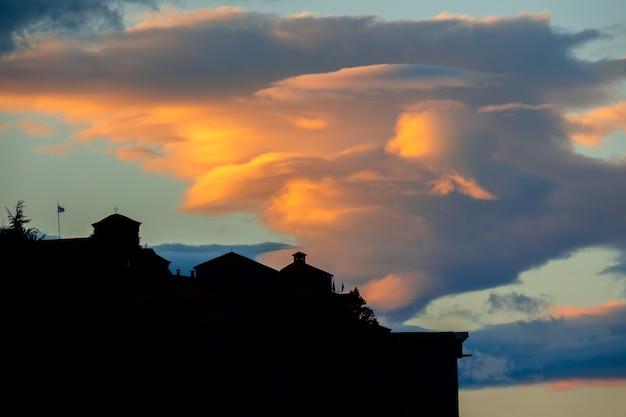 Griechenland. abend in meteora. silhouette eines felsenklosters und einer erstaunlichen wolke
