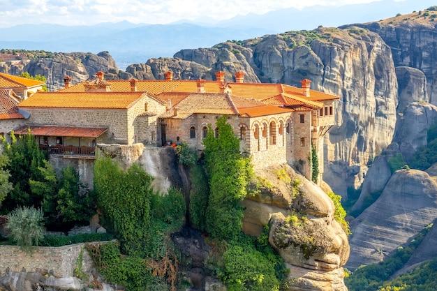 Griechenland. klarer sommertag in meteora. mehrere gebäude eines felsenklosters mit roten dächern gegen große steine