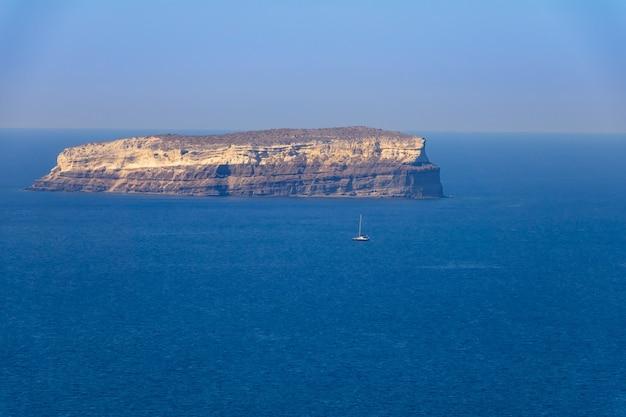 Griechenland. kleine felsige insel an einem sonnigen tag. segelyacht. luftaufnahme