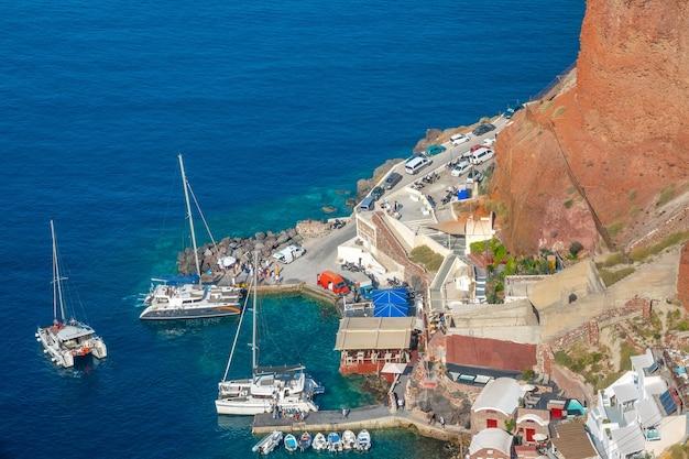 Griechenland. kleiner hafen an der sommerlichen felsküste von santorini. segelkatamarane und motorboote auf dem wasser. viele menschen und autos am ufer