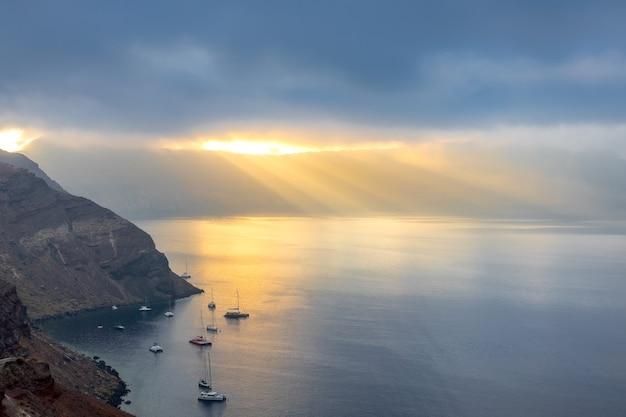 Griechenland. schwere wolken über der caldera von santorini. sonnenstrahlen erhellen die bucht und mehrere vor anker liegende yachten