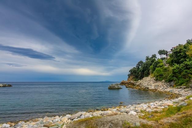 Griechenland. sommer seelandschaft. leeres ufer und eine kleine villa zwischen grünen bäumen