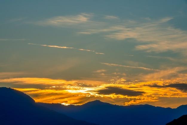 Griechenland. sonnenuntergang über den silhouetten der berge. goldene wolken am dunkelblauen himmel