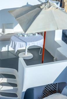 Griechenland. sonniger sommertag auf der caldera der insel santorin. gedeckter tisch unter einem sonnenschirm auf der außenterrasse