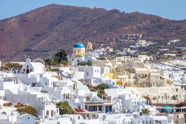 Griechenland. sonniger sommertag auf der insel santorini. weiße gebäude und der berg im hintergrund