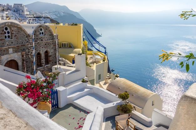 Griechenland. sonniger sommertag auf santorini. gebäude und terrassen mit blumen auf der caldera mit blick auf das meer
