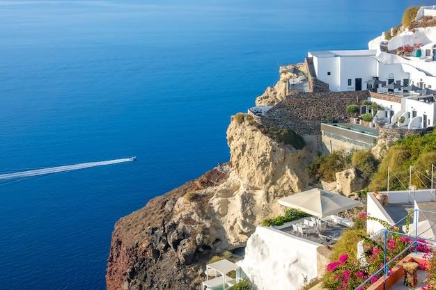 Griechenland. sonniger sommertag auf santorini. gebäude und terrassen mit blumen auf der caldera mit meerblick