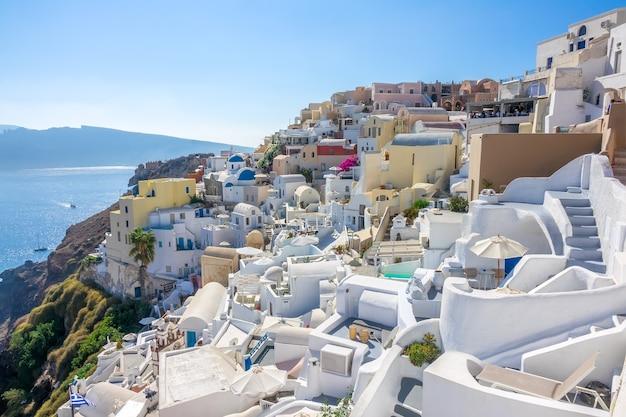 Griechenland. sonniger sommertag auf santorini. oia gebäude und terrassen mit blumen auf der caldera mit meerblick