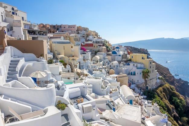 Griechenland. sonniger sommertag auf santorini. weiße häuser in der stadt oia an der caldera und meerblick Premium Fotos