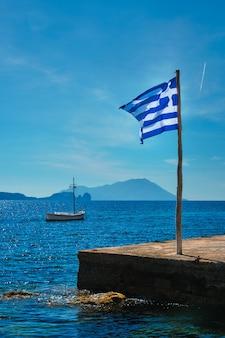 Griechische flagge am blauen himmel auf pier und traditionelles griechisches fischerboot in der ägäis