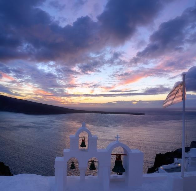 Griechische flagge auf einer lokalen kapelle in oia, santorini, griechenland