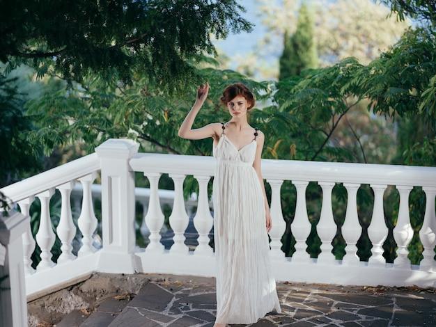 Griechische frau im weißen kleid posiert im park