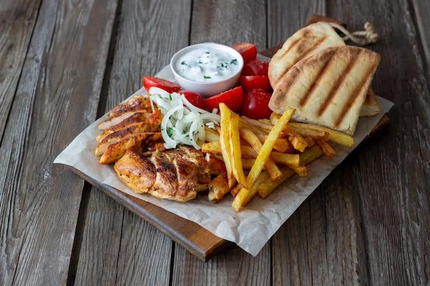 Griechische gericht gyros mit huhn, pommes frites, tomaten, zwiebeln und pita. griechische küche.