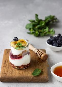 Griechische joghurtparfaits aus müsli, heidelbeeren und bananen in einmachgläsern