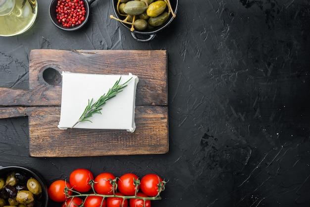 Griechische salatzutaten des käse-feta, auf schwarzem hintergrund, flach mit kopierraum für text