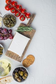 Griechische salatzutaten des käse-feta, auf weißem hintergrund, flach mit kopierraum für text