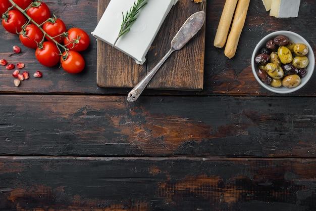 Griechische salatzutaten eingestellt, auf dunklem hölzernem hintergrund, flach liegen mit kopienraum für text