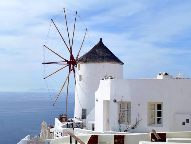 Griechische windmühle der traditionellen art und weißes landhaus in oia-dorf auf santorini-insel, griechenland