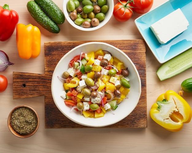 Griechischer dorfsalat horiatiki mit feta-käse, oliven, pfeffer, tomaten, gurke und roten zwiebeln