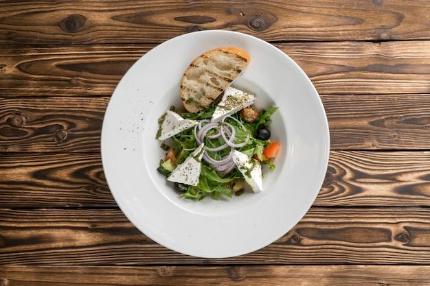 Griechischer gemüsesalat mit feta-käse, rucola, gurken, zwiebeln, tomaten, oliven und gegrilltem ciabatta