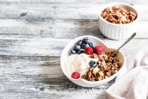 Griechischer joghurt, blaubeeren, himbeeren und granola in einer weißen schüssel