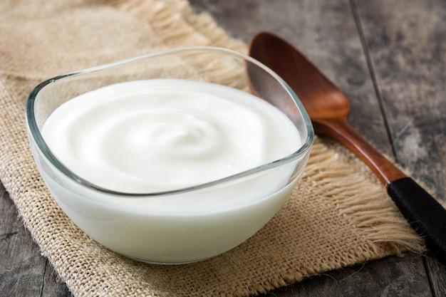 Griechischer joghurt in der glasschüssel auf holztisch