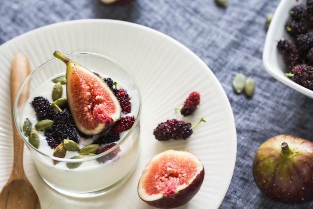 Griechischer joghurt mit feigen, maulbeeren und kürbiskernen