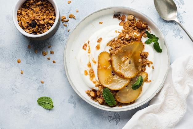 Griechischer joghurt mit karamellisierter birne, müsli, nüssen und geschmolzenem zucker für ein gesundes frühstück auf einer grauen keramikplatte. rustikaler stil. draufsicht.