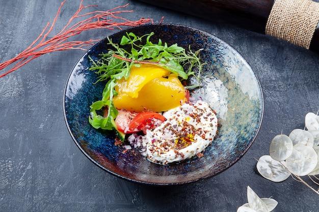 Griechischer joghurt mit olivenöl, gewürzen mit gebackenem gemüse, paprika und tomate in dunkler schüssel. gesundes, veganes essen für diätmenüs. lebensmittel foto hintergrund