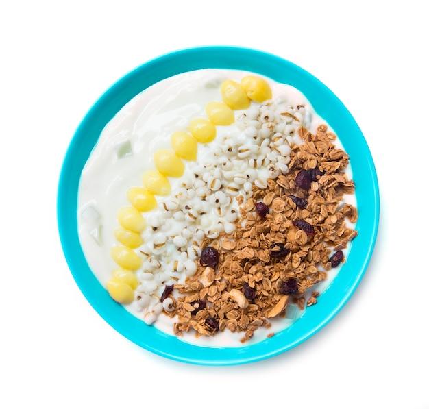 Griechischer joghurt und müsli, trockene rote moosbeere und gekochtes ginko- und adlaykorn ist ein mahlzeitersatz für die draufsicht des healthyfood und der diät, die lokalisiert wird