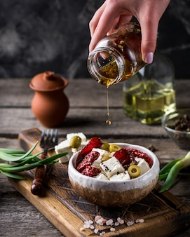 Griechischer käsefeta mit kräutern und oliven, getrocknete tomaten.