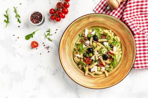 Griechischer nudelsalat mit tomaten, avocado, schwarzen oliven, roten zwiebeln und käsefeta. frisch, salat, banner, menü, rezept. gesundes essen