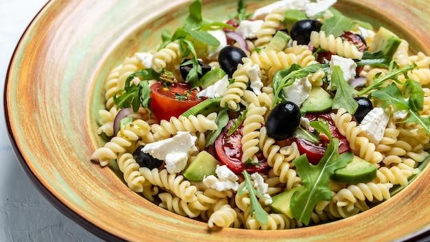Griechischer nudelsalat mit tomaten, avocado, schwarzen oliven, roten zwiebeln und käsefeta. hintergrund für lebensmittelrezepte. nahansicht.
